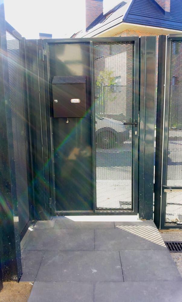 Puerta batiente peatonal, vista desde el interior, con buzón integrado (e7384)