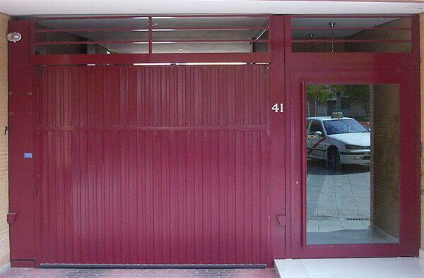 Basculante 2 hojas, en chapa plegada y zona superior en barrotes para ventilación. Puerta peatonal en cristal a un lateral (e4264)