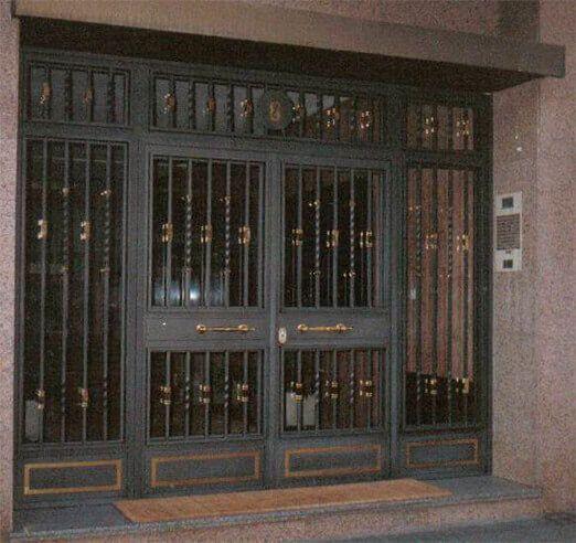 Portal batiente 2 hojas con partes fijas barrotes y motivos en forja